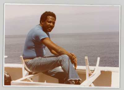 Black male sitting on deck of ship with sea in background