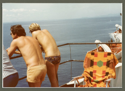 two males on deck of ship. both are shirtless. one is wearing a speedo and the other is wearing shorts. They are leaning on railing.