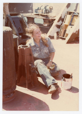 Female cadet sitting next to paint can