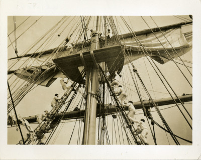 Cadets climbing rigging on ship.