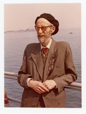 man wearing beret and suit standing on deck
