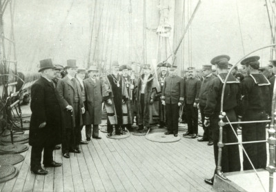 Men standing around on ship deck in formal clothing.