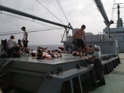 Cadets socializing on the  #2 cargo hatch out in the sun.