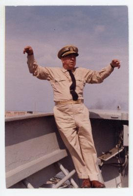 man standing on deck with arms raised