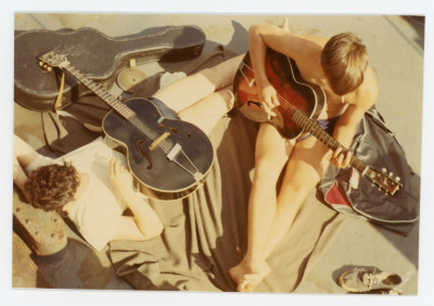 Shirtless seated male student playing guitar with second guitar lying on ground next to him.
