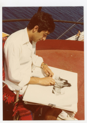 Image of student with sketch book in lap on deck of ship.
