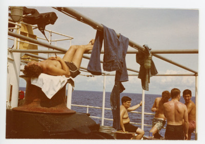 laundry hanging over poles and students hanging out on deck of ship