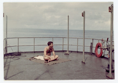 Students with legs crossed sitting on blanket on ship deck