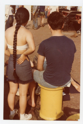 female student with long braid standing next to make student sitting