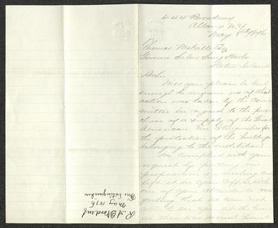 This letter is handwritten with brown ink on cream-colored paper with blue lines. The sheet has a distinct vertical fold down the length of the paper. On the right half is the first page of the letter; the left half is blank, except for a notation, oriented perpendicular to the letter's text, with the name of the sender, date, and subject, presumably for filing purposes.