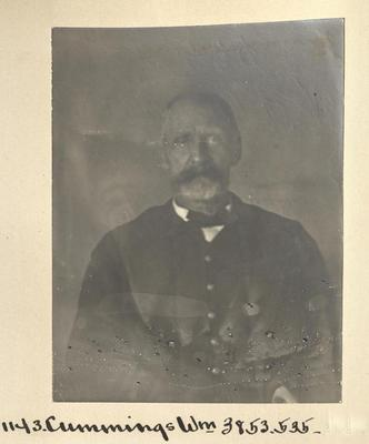 Black and white photograph of a seated man, viewed from the waist up. He has a large mustache and wears a dark suit, white collar, and bow-tie.