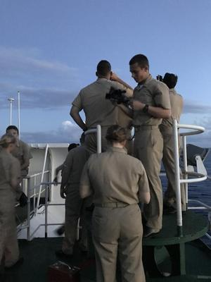 Group of students in uniforms holding sextants on deck of ship at dusk.