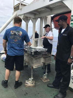 The cooks on the ship prepares hamburgers, hot dogs, and steaks for the cadet on a Sunday.