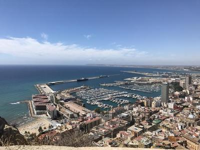 Looking at the city of Alicante, Spain from the top of Santa Barbara Castle. Houses, beach, ships, and the Training Ship Empire State VI is spotted.