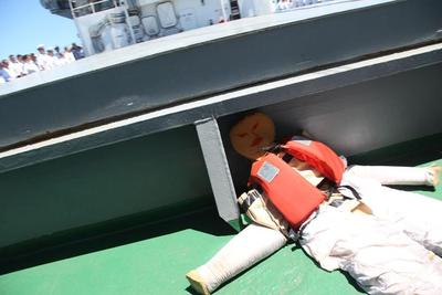 On the green deck of the ship lies Oscar, a sponge dummy dressed in a tanned boiler suit.