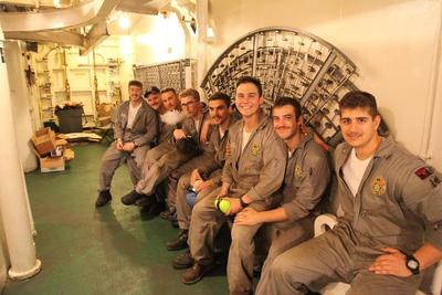 Eight 1st Class (Senior) cadets in grey boiler suits are sitting on a bench and are ready to head down to the Engine Room.