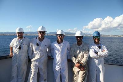 Presenting 4 deck mates and the chief mate (in the middle) in white boiler suits and hardcovers with a port in the distance.
