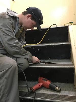 A 1st Class (Senior) Cadet, who is a Carpenter) is working on the staircase (ladderwell) of the ship.