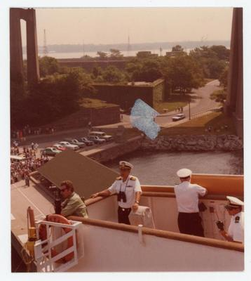 Four officers, three in dress uniform and one in casual clothes, are standing on the port side of the bridge, getting ready to leave. In a distance are the cadets' parents who are watching the ship leave.