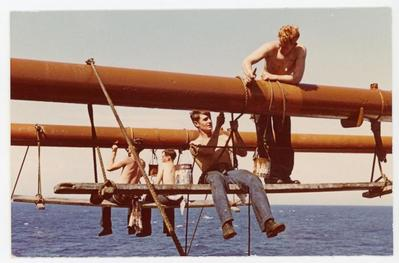 Four cadets are painting over parts of the ship aloft in a seat consisting of a board and a rope on the TSES IV in the scorching sun.