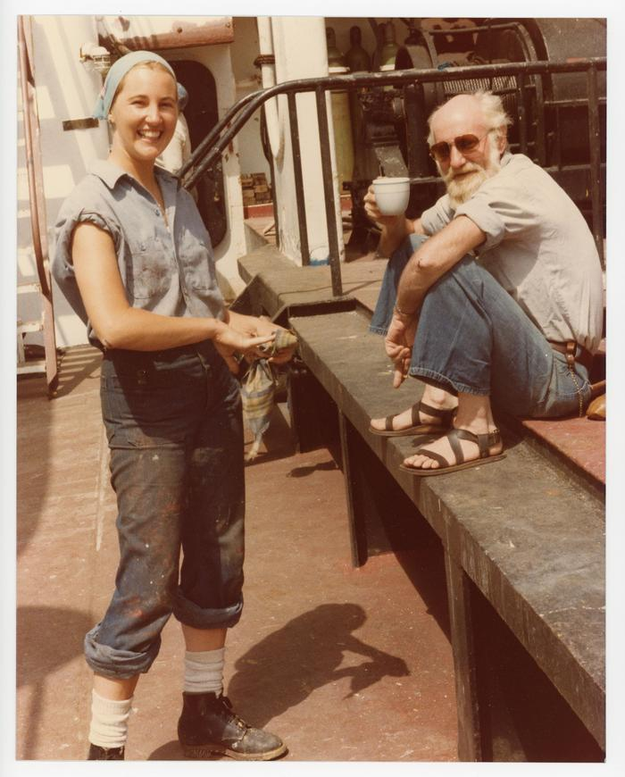 Female cadet with rolled up sleeves and dirty work uniform next to seated man holding a coffee cup, wearing sandals and sunglasses.