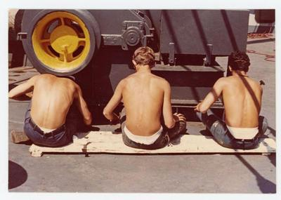 Three cadets are working on a yellow and grey machinery on deck under the scorching sun.