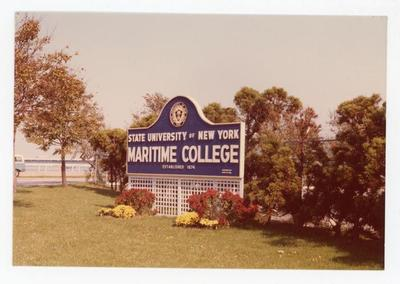 In a distance lies the SUNY Maritime College sign with trees and bushes behind it.