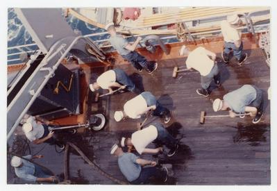 Ten cadets are scrubbing the deck of the ship with deck scrub brushes.