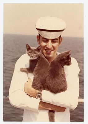 A cadet in his sailor outfit is happily, hugging onto two blackish-grey cats.