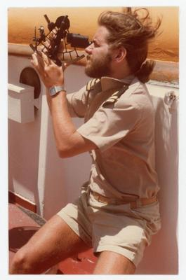 The mate on a watch is taking an angular measurement between the sun and the visible horizon with his sextant.