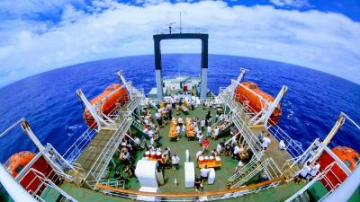 view of ship's deck with people hanging out and eating and bright blue sea and white clouds in background