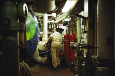 Male student in boiler suit in bowels of ship, facing away from camera