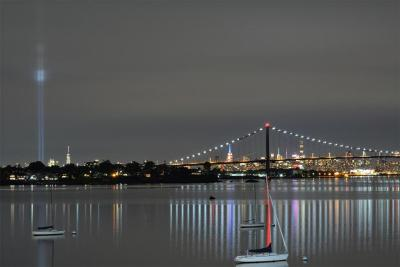 Manhattan skyline and Whitestone Bridge in distance at night with  boats on water in foreground