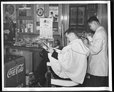 Image of student getting hair cut in barbershop with canteen in background.